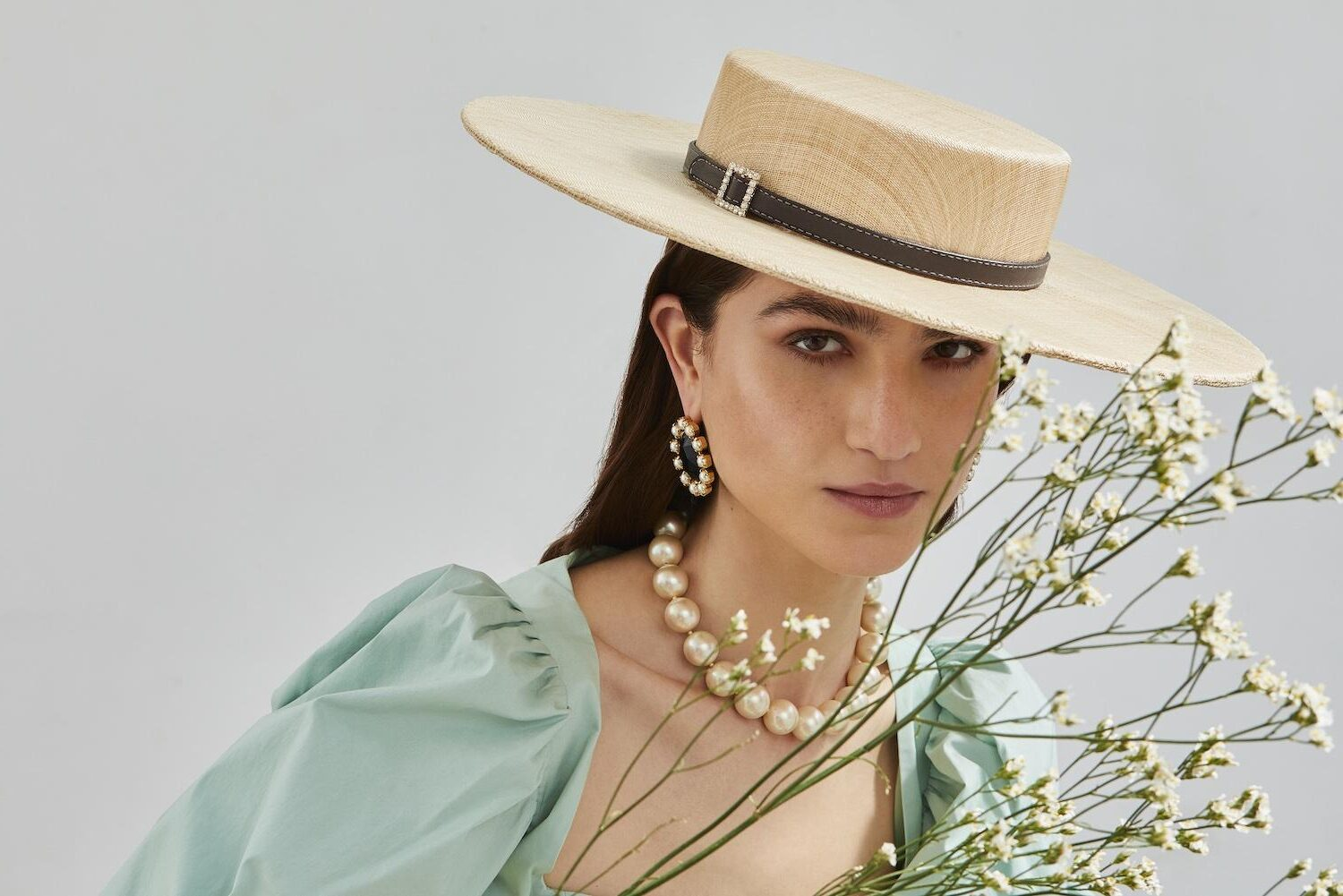 Wide-brimmed natural straw super-boater with leather belt and crystal buckle on model